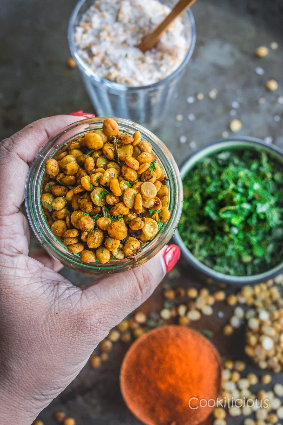 a hand holding a jar filled with Crispy Vegan Split Peas with kasoori methi, paprika and himalayan salt in the background