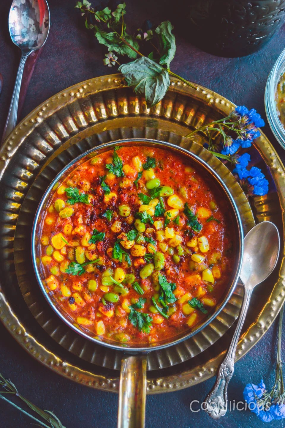 a bowl of Edamame & Sweet Corn Gravy placed over a set of beautiful brass plates