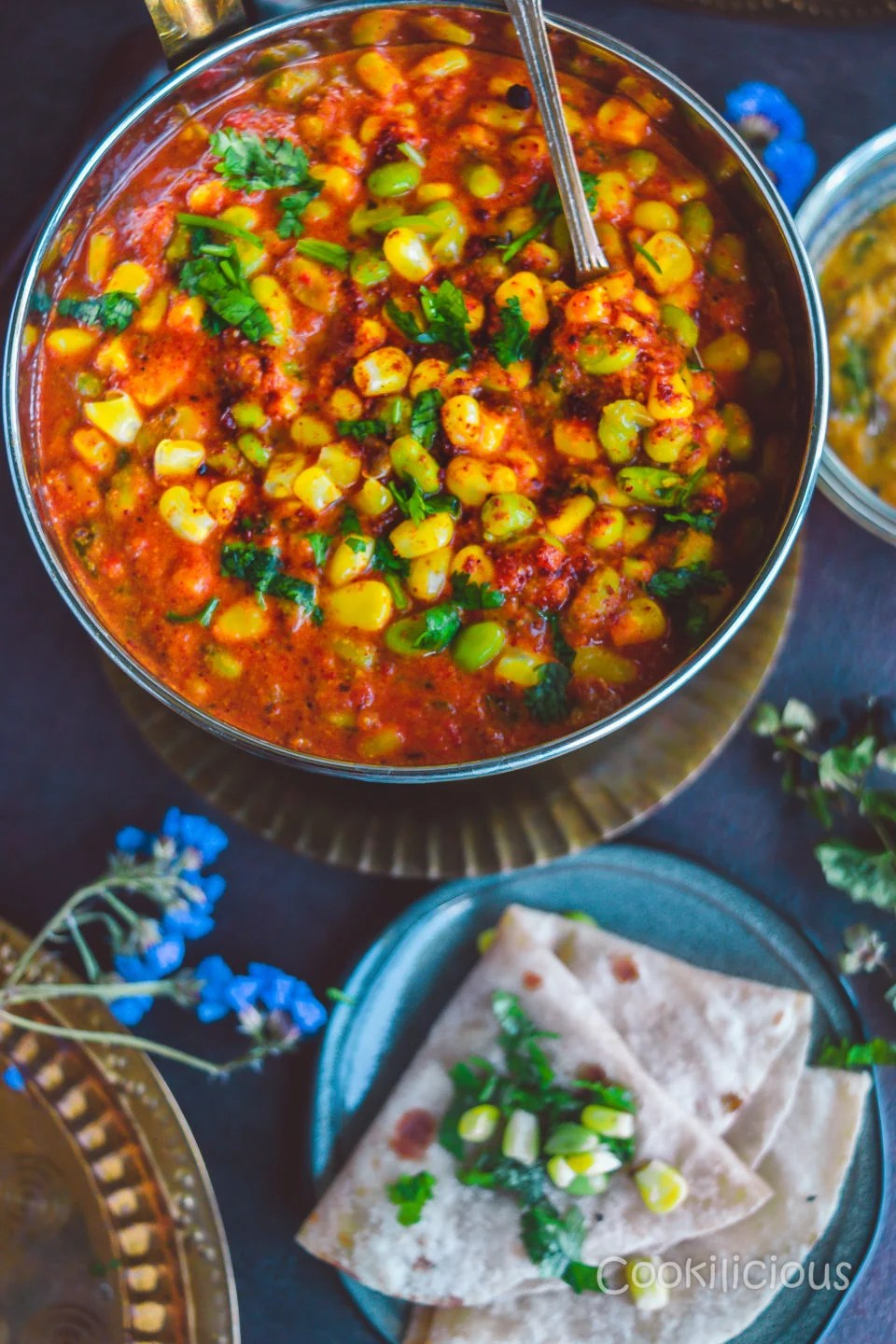 flat lay image of a bowl of Edamame & Sweet Corn Gravy served with chapati