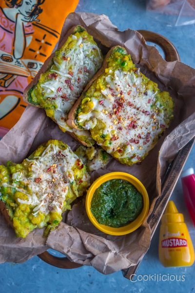 Potato Chilly Garlic Masala Toast served in a tray over crumbled paper with a bowl of green chutney on the side