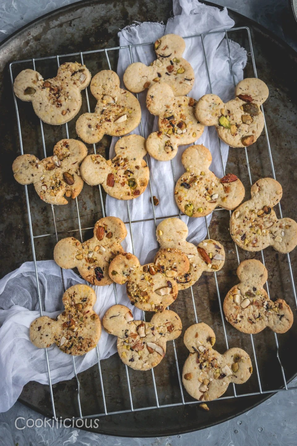 Eggless Kesar Pista Badam Biscuits/Saffron Cashew Almond Cookies resting on a rack with muslin cloth underneath it