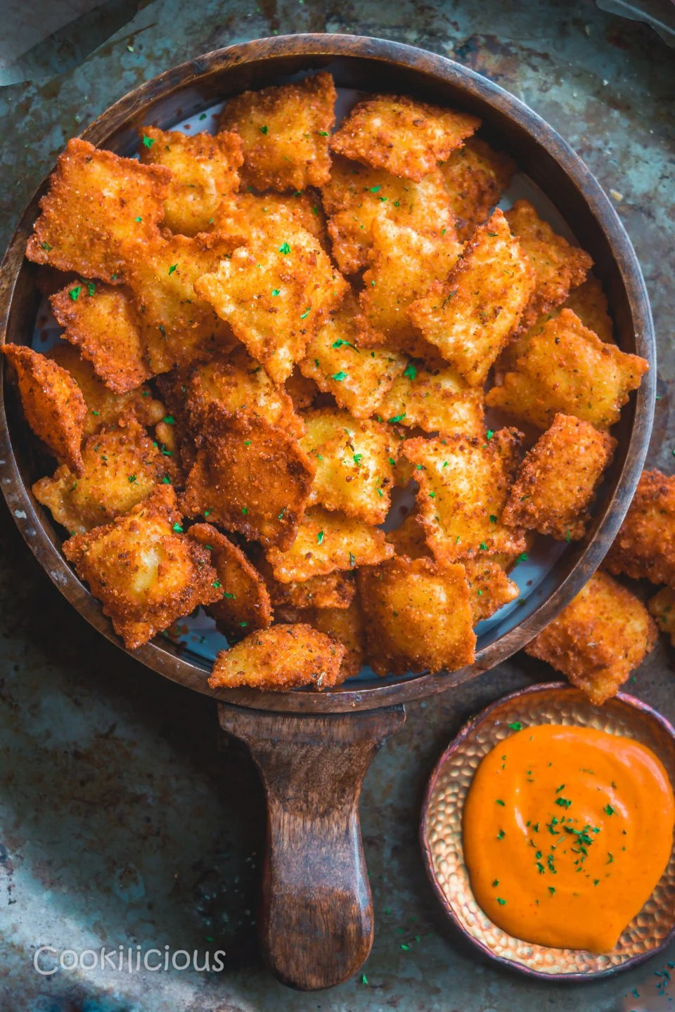 a round tray filled with Copycat Olive Garden Cheesy Fried Ravioli