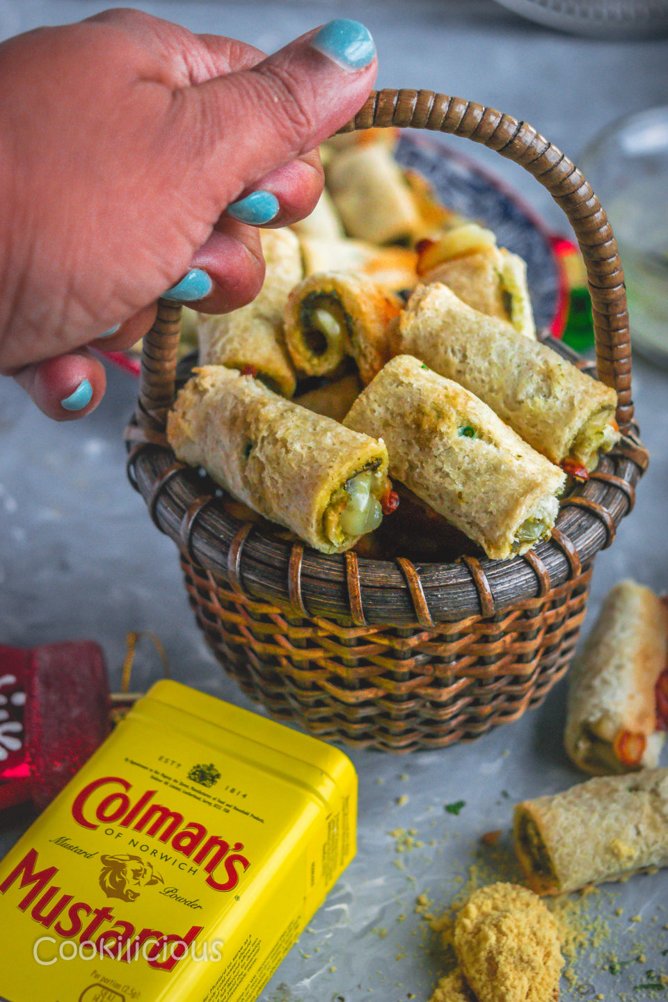 a hand holding a basket filled with Baked Bread & Chutney Rolls