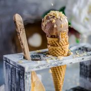 A hand sprinkling coconut chips over a Coconut Chocolate Dairy-Free Ice Cream cone placed in an ice cream stand and a wooden spoon besides it