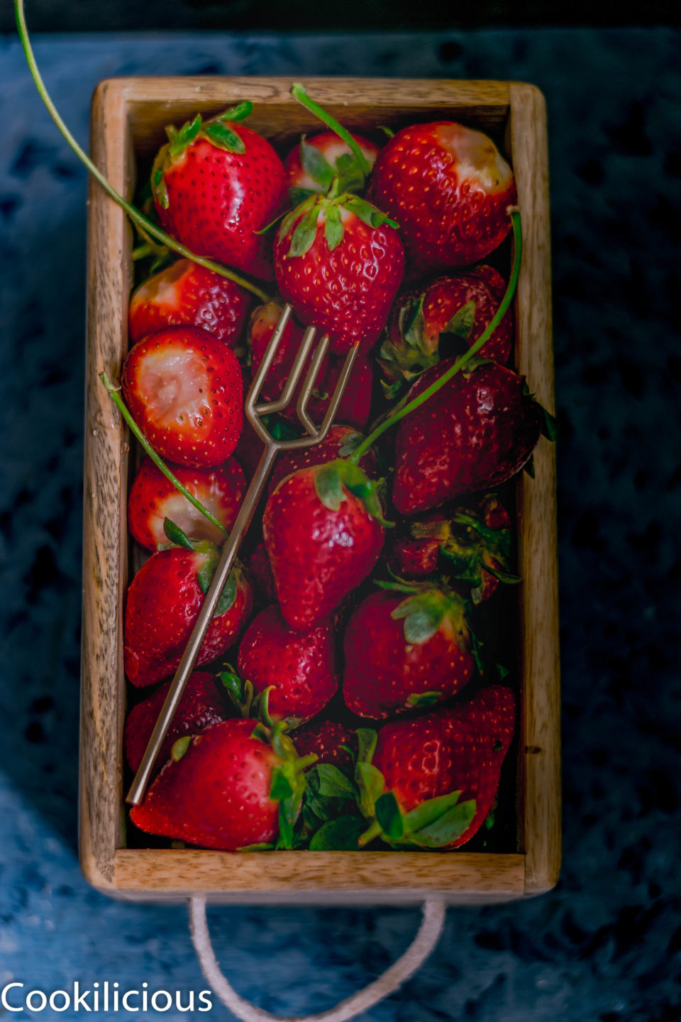 fresh strawberries in a wooden box that will be used to prepare Tropical Orange Strawberry Spritzer