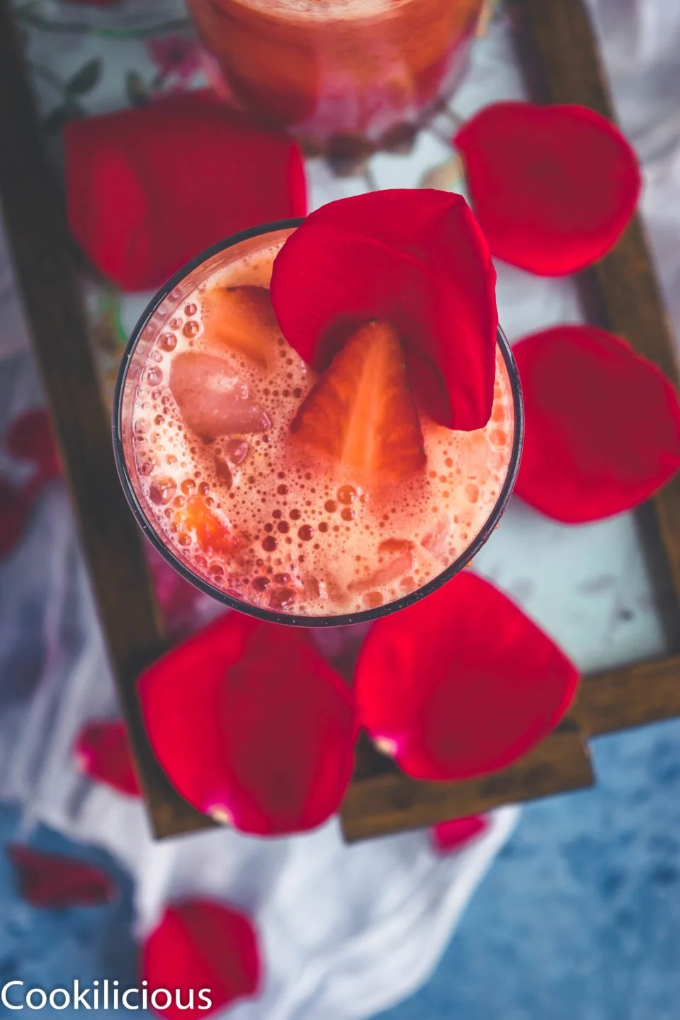 top angle shot of a glass filled with Tropical Orange Strawberry Spritzer garnished with a strawberry slice and a rose petal