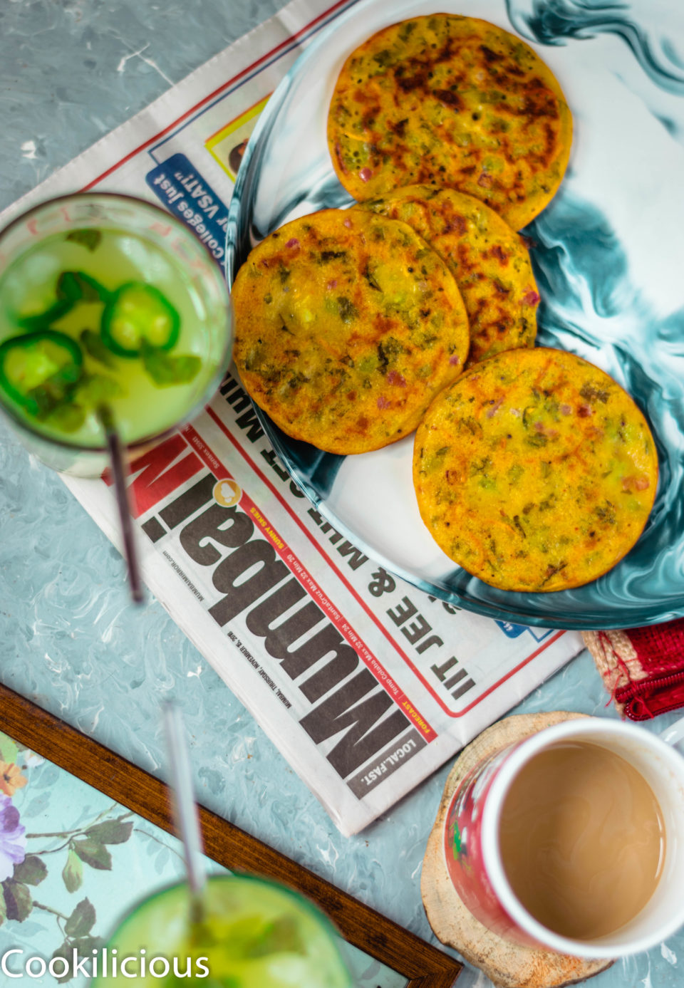 3 to 4 Mini Masala Uttapam placed in a plate with a glass of juice and tea next to it