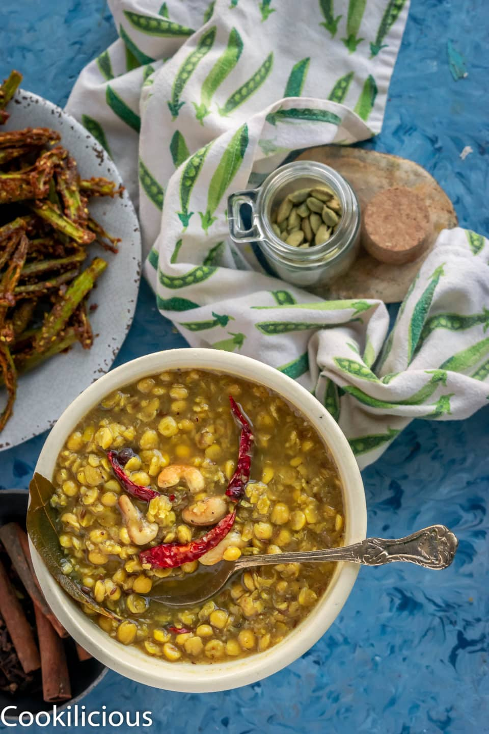 a bowl of Bengali Style Cholar Dal With Chana Dal with a kitchen towel and a bottle of cardamom next to it