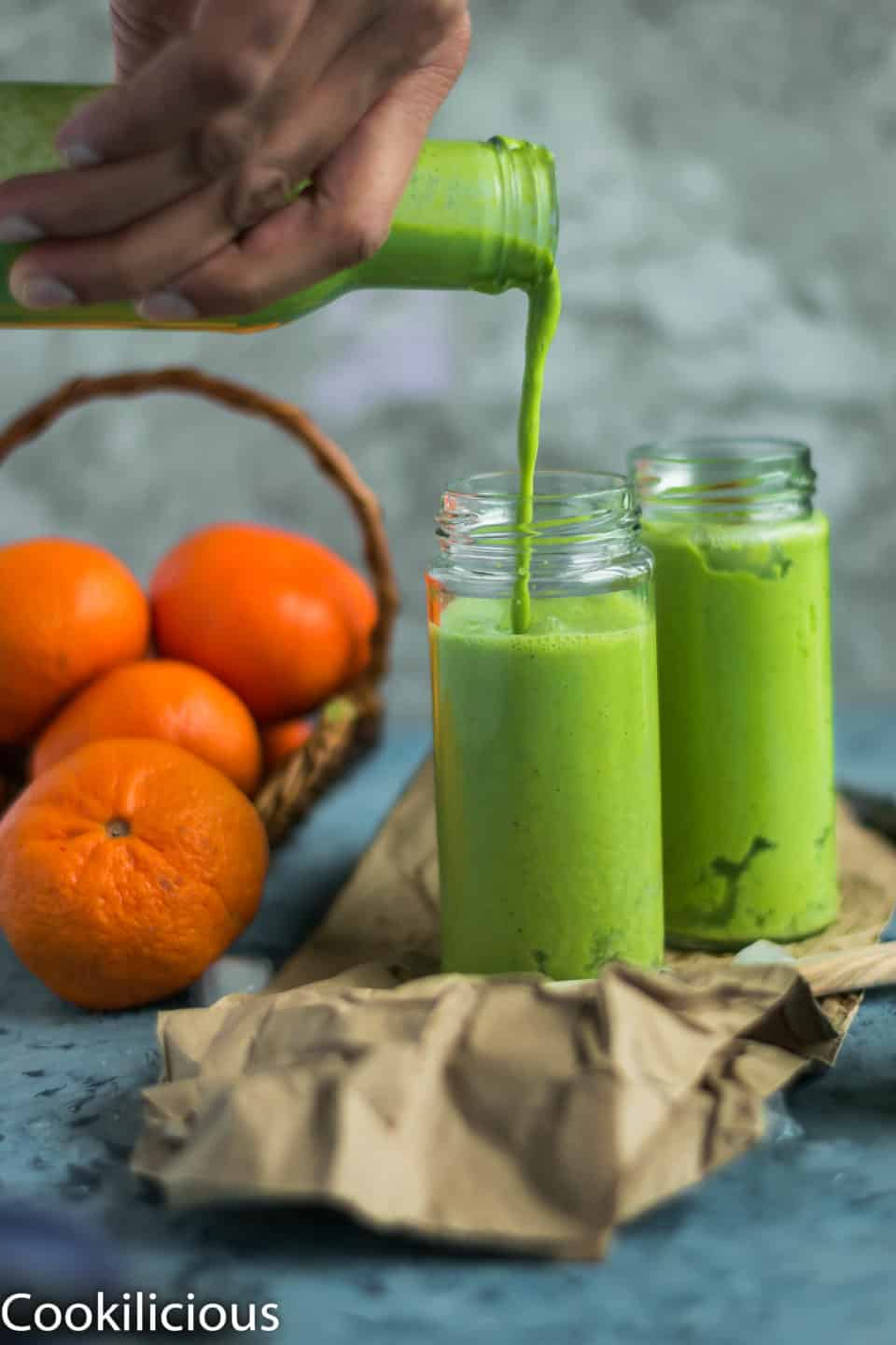 a hand holding a bottle and pouring Super Healthy Mango Spinach Yogurt Power Smoothie into a glass