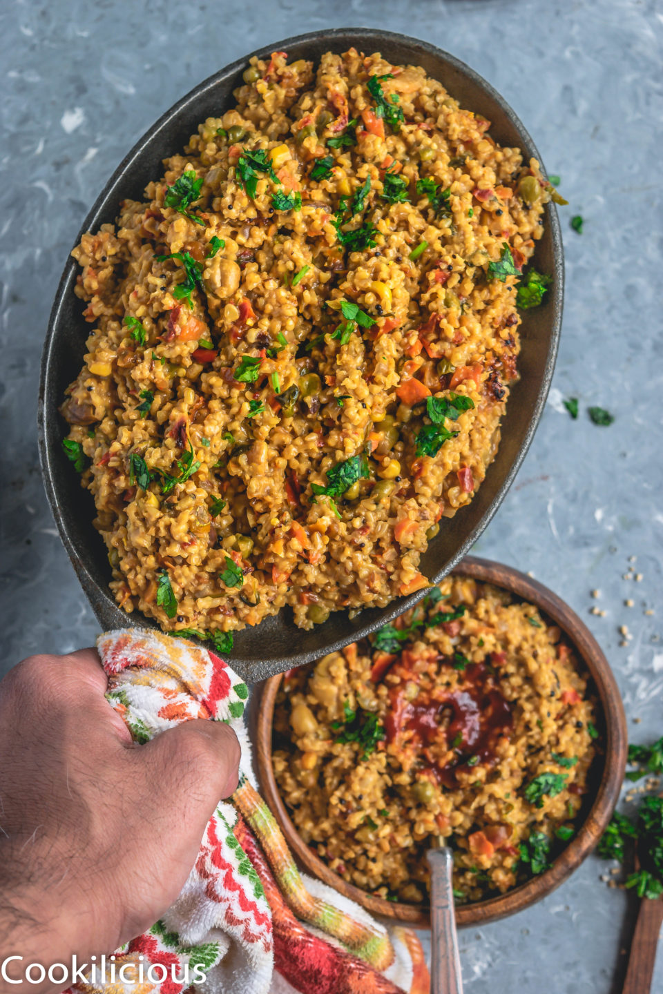 a hand holding an oval platter filled with Instant Pot Oats & Vegetable Upma