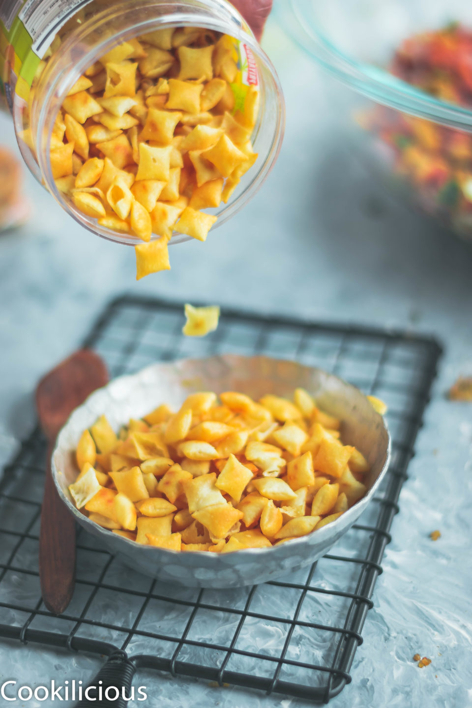 a hand pouring a bottle full of cheeselings onto a bowl