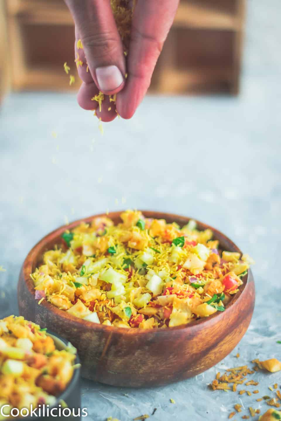 a hand sprinkling sev over 2 bowls containing Crispy & Masaledar Cheeselings Bhel