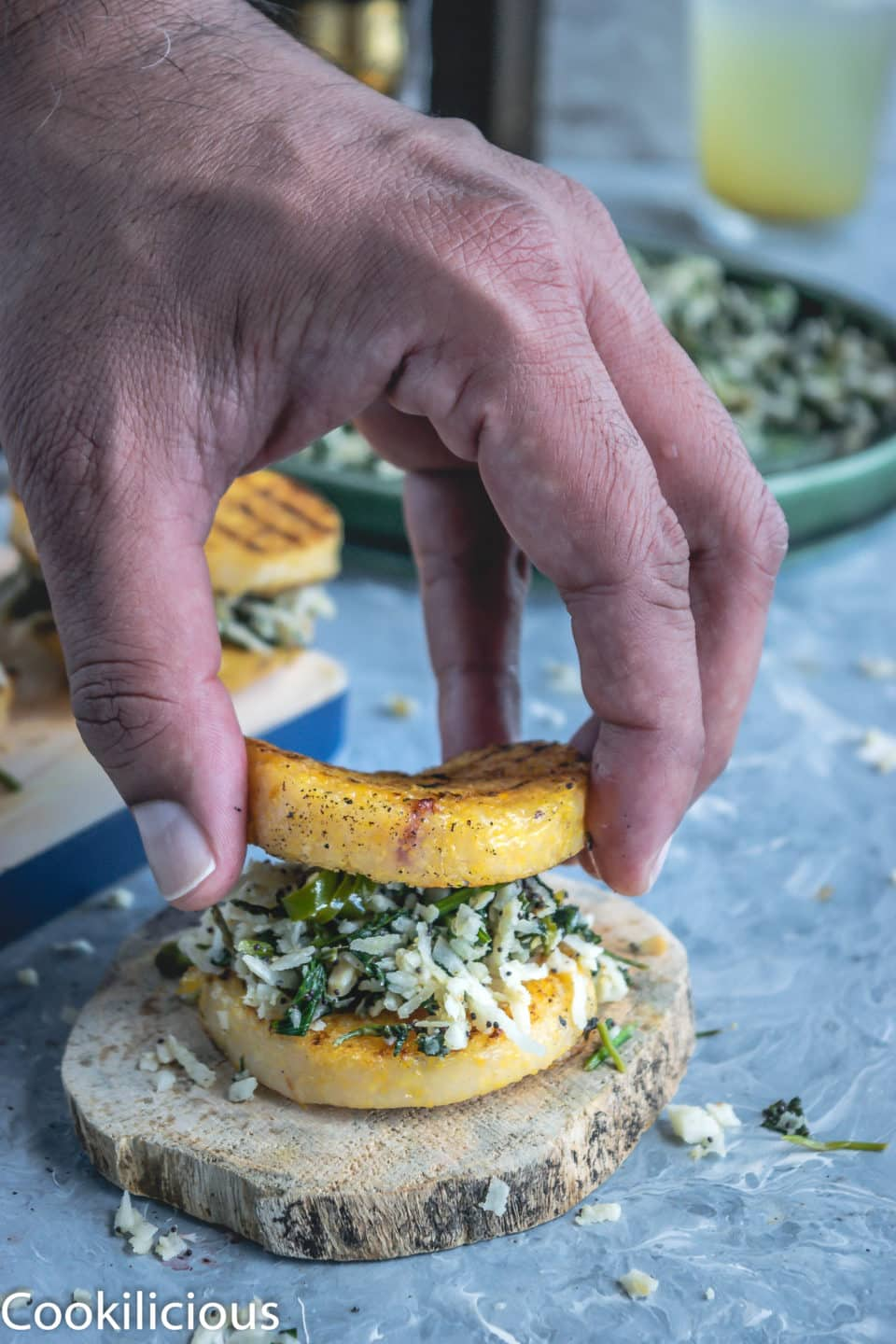 a hand placing a grilled polenta over the prepared cilantro masala, like a sandwich makes a great vegan gluten free recipes