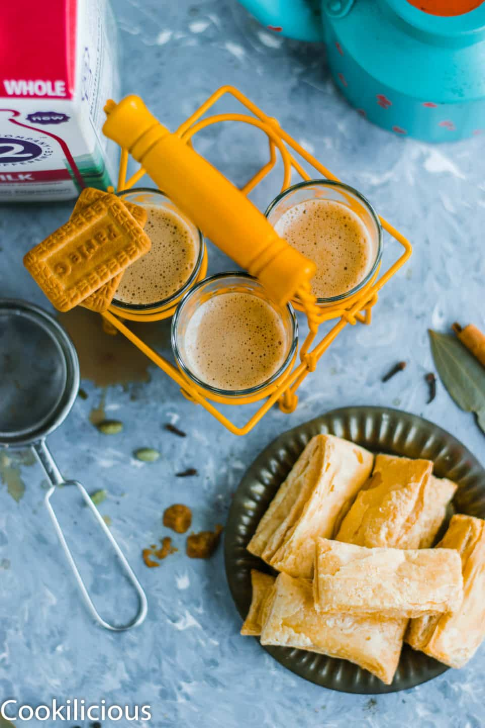 top angle shot of masala chai in a chai stand with a biscuit resting on top of one glass and a plate full of khari on the side