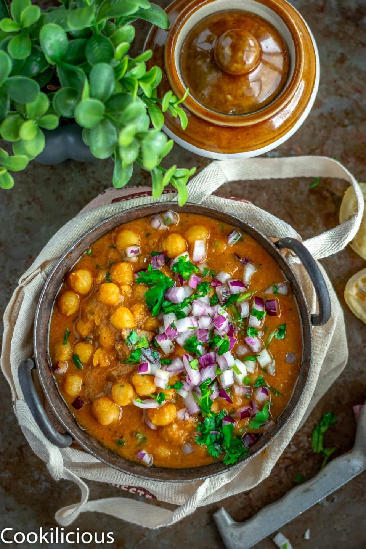 South Indian Chickpeas Curry | Chettinad Kondai Kadalai Kuzhambu in a kadai with a jar on the side of it