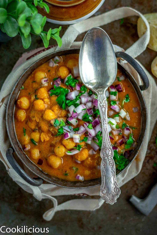 a spoon resting over a kadai full of South Indian Chickpeas Curry | Chettinad Kondai Kadalai Kuzhambu