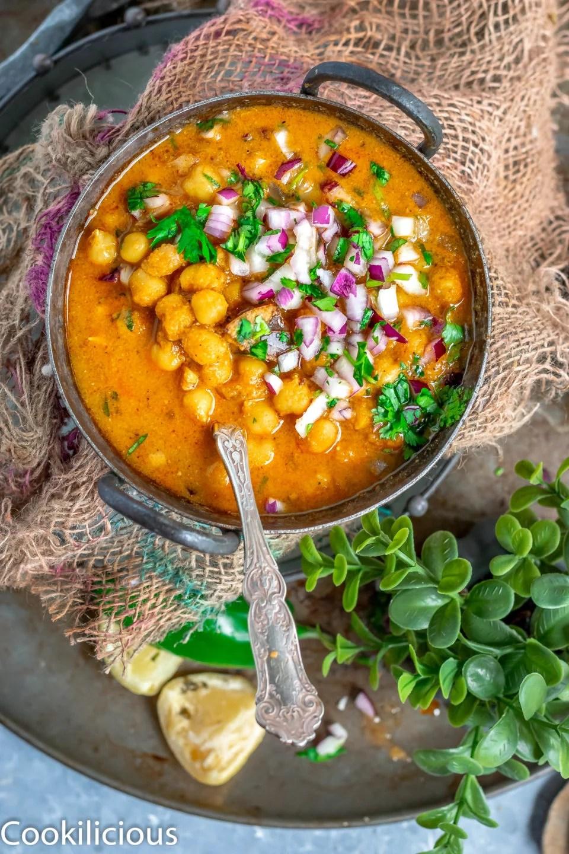 South Indian Chickpeas Curry | Chettinad Kondai Kadalai Kuzhambu in a kadai with a bunch of cilantro on the side
