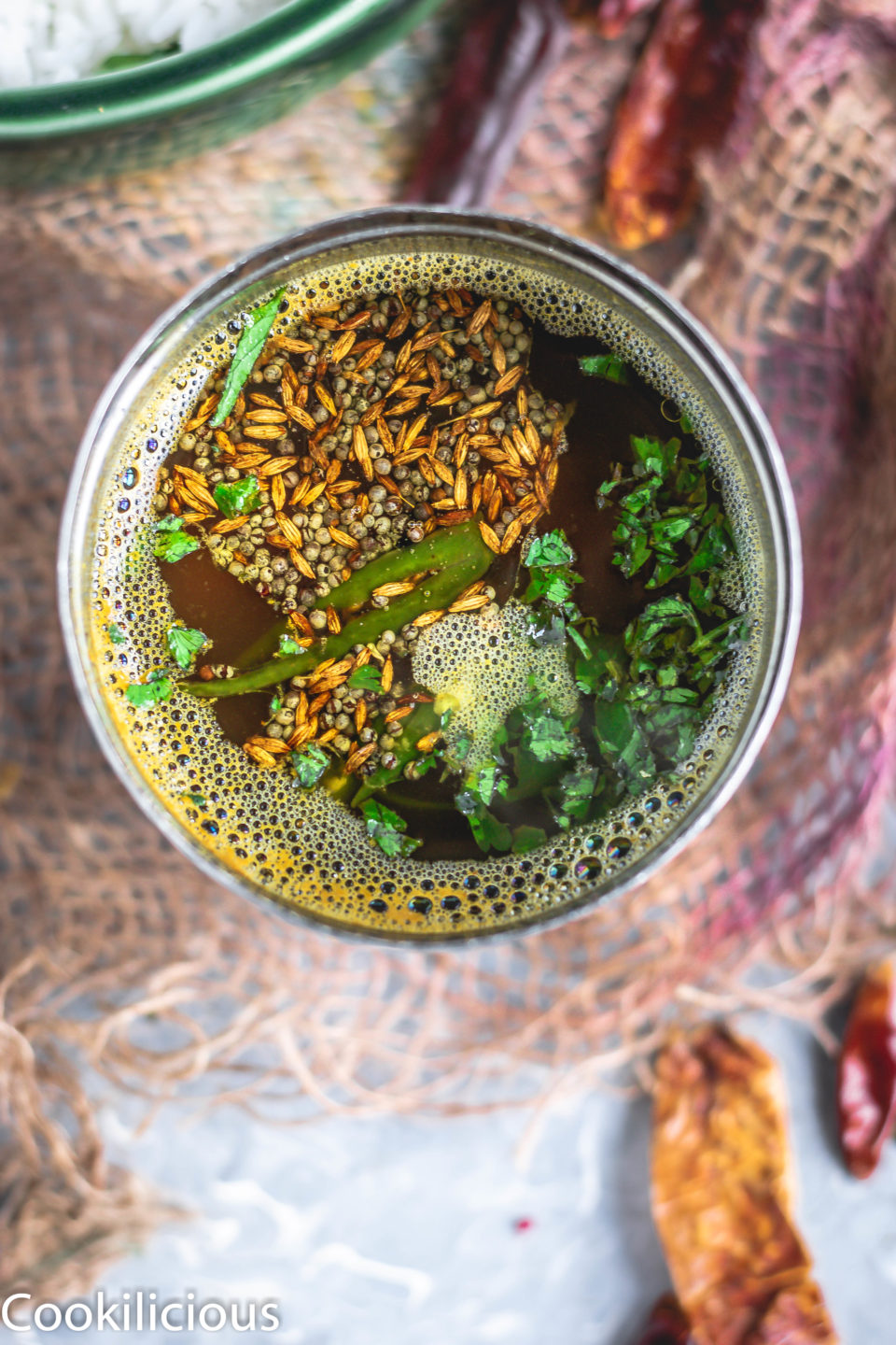 top angle shot of South Indian Tomato Rasam With Pink Lentils in a steel vessel with tadka on top