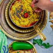 Besan pitla in a bowl and a hand reaching out into it with a piece of bhakri