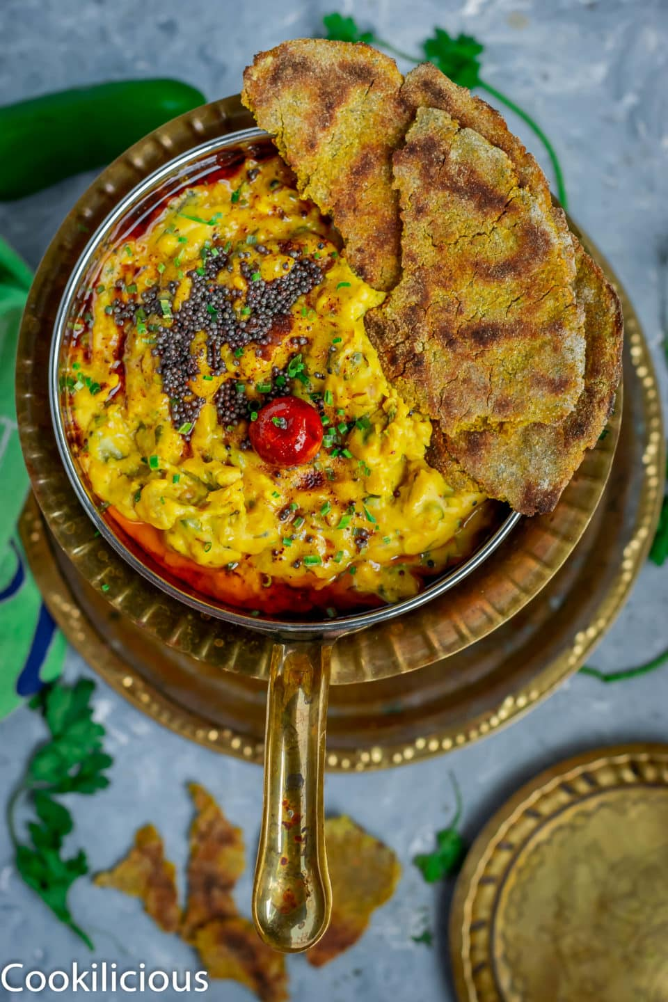 top angle shot of besan pitla in a bowl with bhakri pieces over it