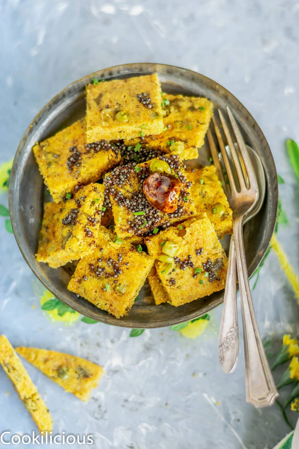 Corn Dhokla in a plate with tadka on top and cutlery on the side