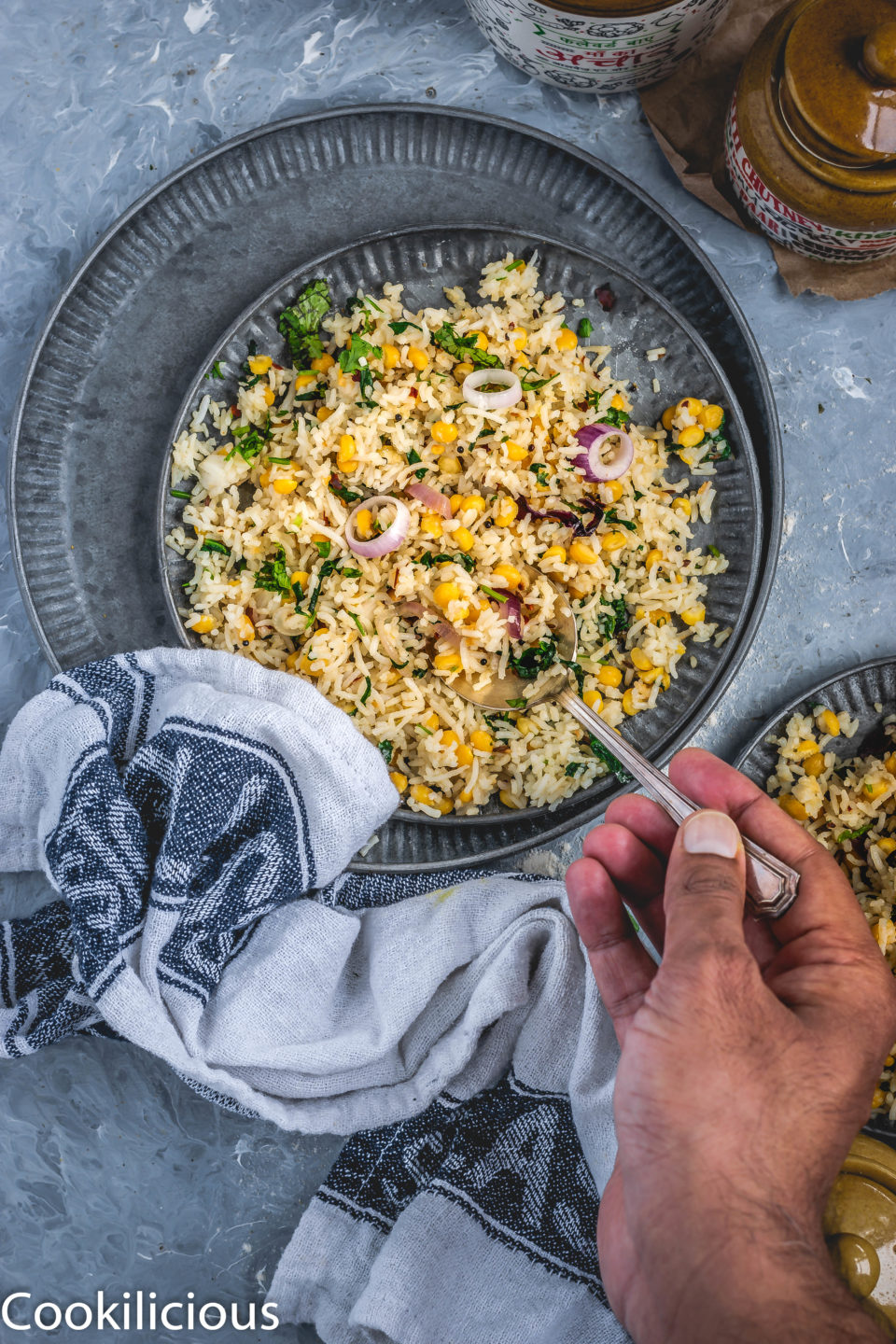 a hand holding a spoon and digging into a plate full of Cilantro, Spinach & Lentil Rice