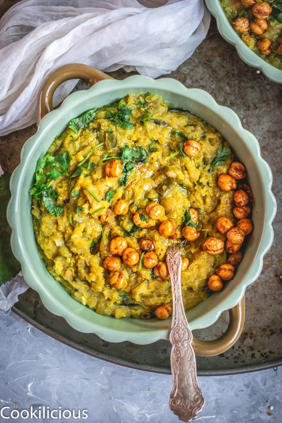 top angle shot of a bowl full of Instant Pot Quinoa & Chickpeas Khichdi with a spoon in it