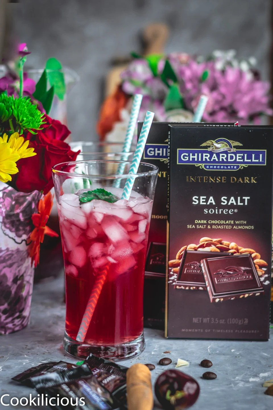 a glass of Cherry Lemon Iced Tea with a straw in it and Ghirardelli dark chocolate on the side