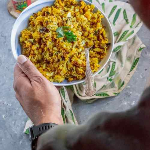 pair of hands holding a bowl of Cabbage & Chickpea Flour/Besan Stir-Fry