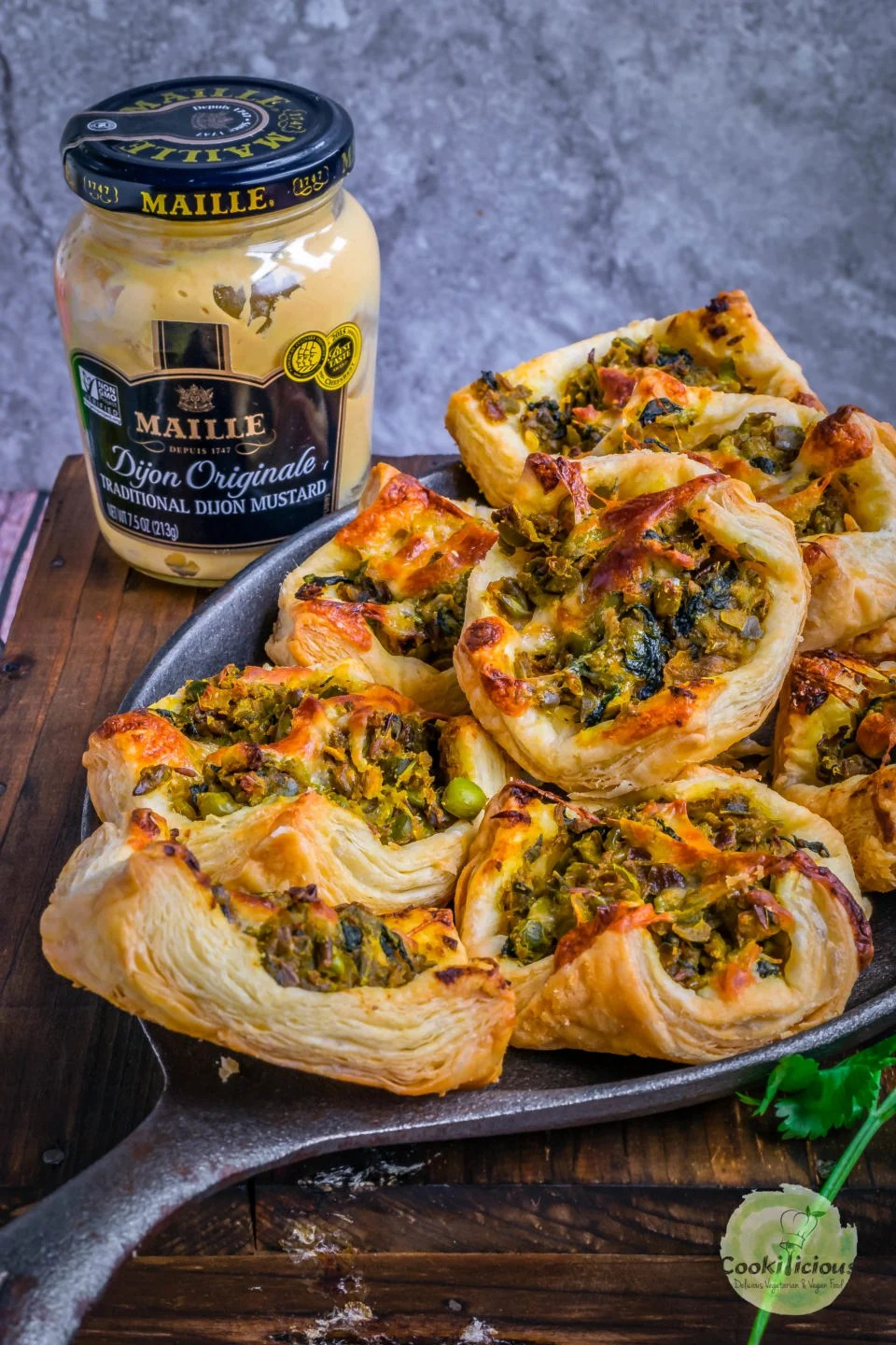 side view of Spicy Green Peas & Spinach Pastry Puffs with a jar of mustard sauce on the side