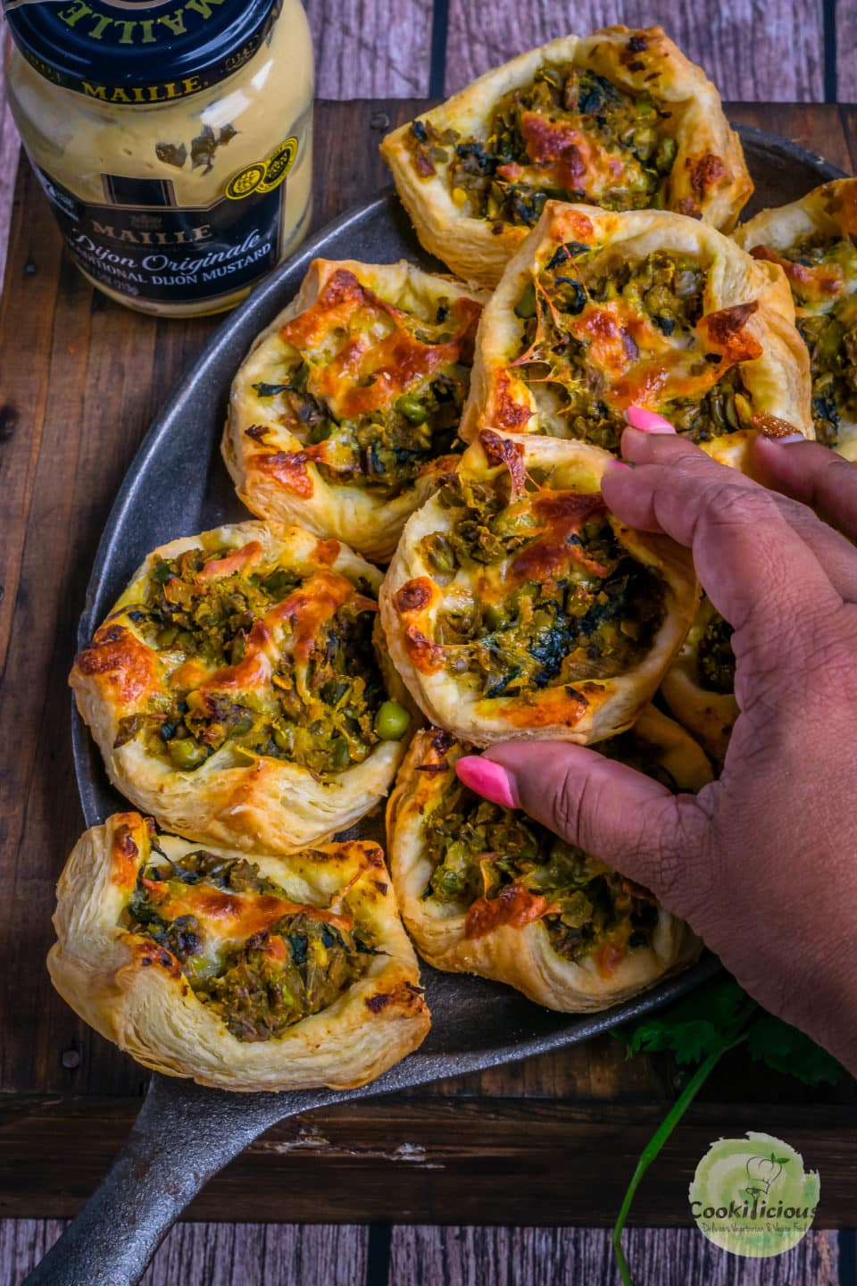 a hand picking up on Spicy Green Peas & Spinach Pastry Puff from the tray