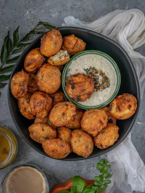 a bowl of Dill Flavored Lentil Fritters with a small chutney bowl in it