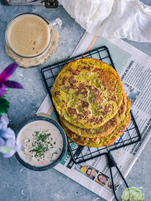 flat lay image of Lentil Pancakes with Leftover Dal with a bowl of yogurt dip and a coffee mug on the side