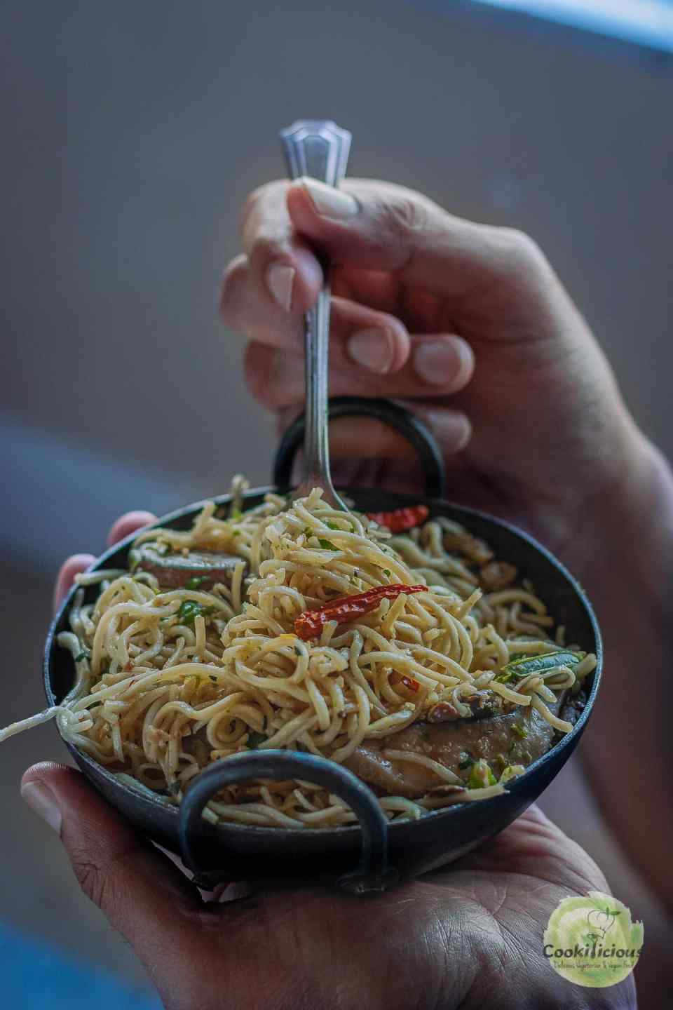a set of hands enjoying a bowl of Chilly Garlic Noodles