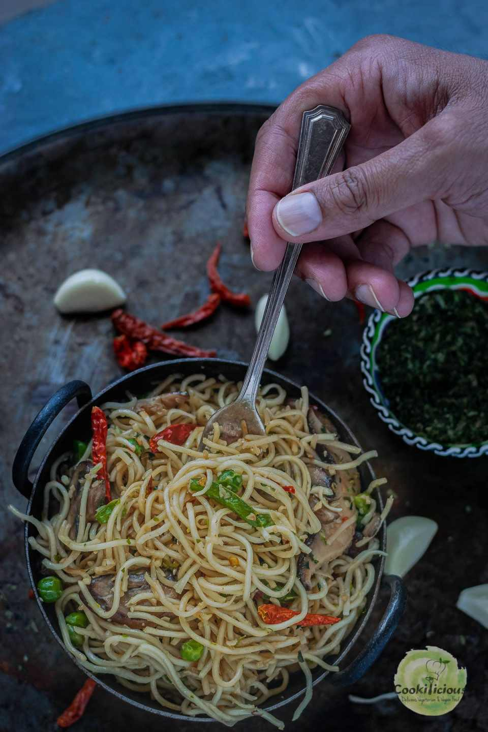 close up shot of a hand digging a fork into a bowl of Chilly Garlic Noodles