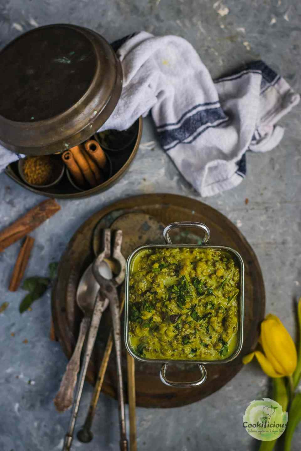 a square bowl filled with mung bean sprouts Coconut Indian vegan recipe and cutlery on the side and a kitchen towel on the top