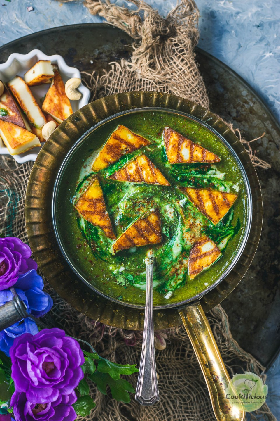 Restaurant Style Palak Paneer served in a round platter with a spoon in it