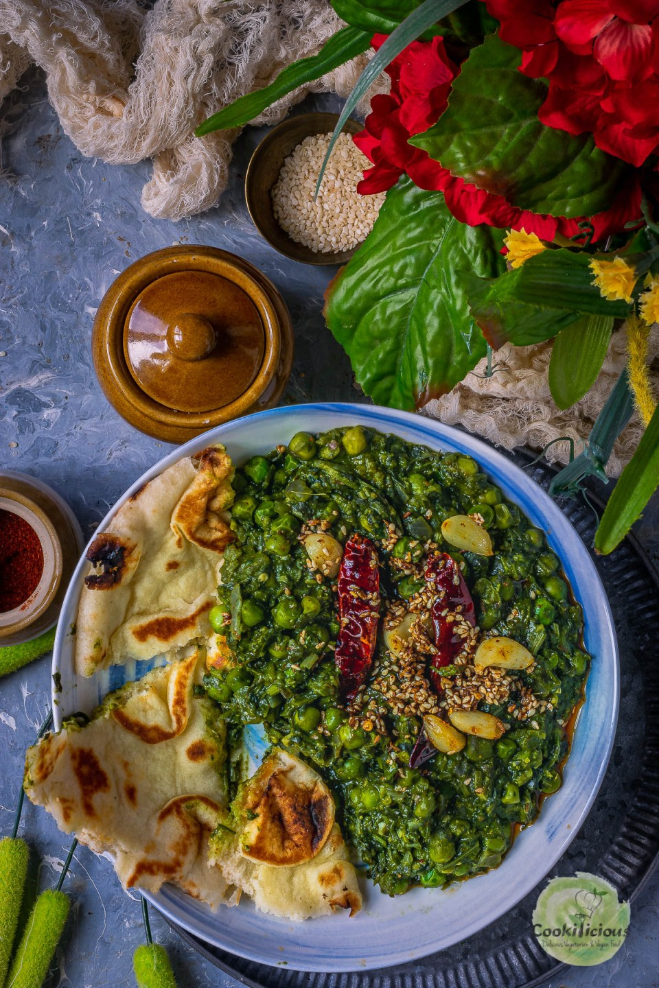Garlicky Peas Spinach Fenugreek Curry served in a round bowl with pieces of naan next to it