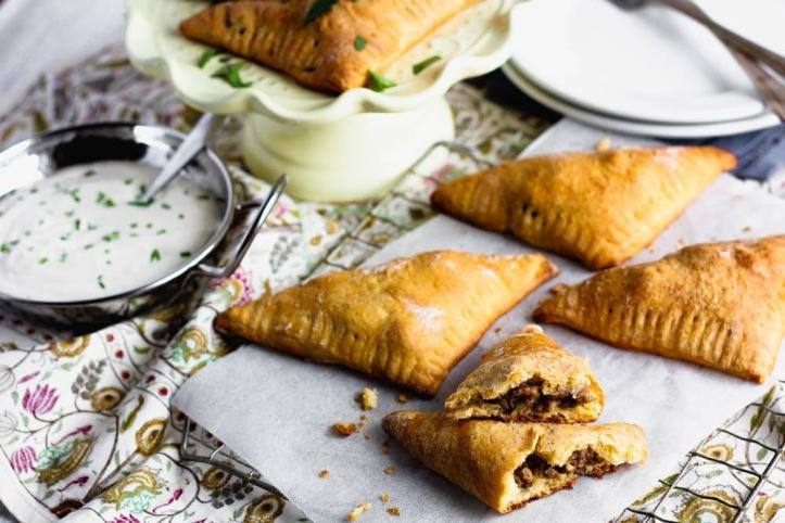 golden brown triangular beef stuffed pastries beside a small metal bowl of white sauce garnished with green herbs