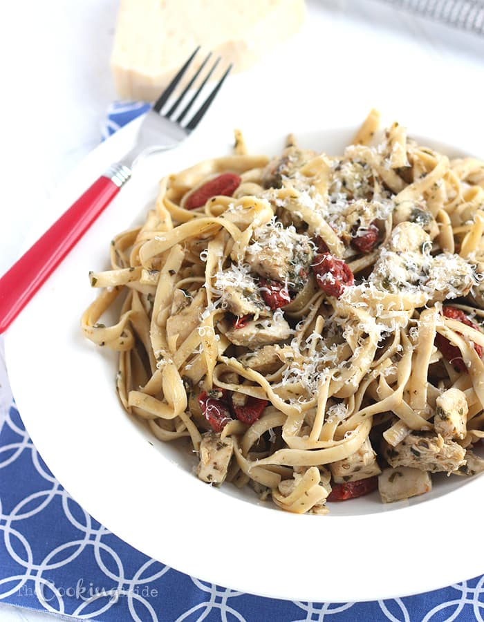Delicious fettuccine recipe is dressed up with yummy sundried tomatoes, basil pesto, grilled chicken and freshly grated Parmesan cheese.