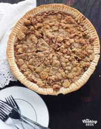 Southern sweet potato pie recipe is made with fresh roasted sweet potatoes, bourbon and molasses. It's topped with a sugary, crunchy praline pecan topping.