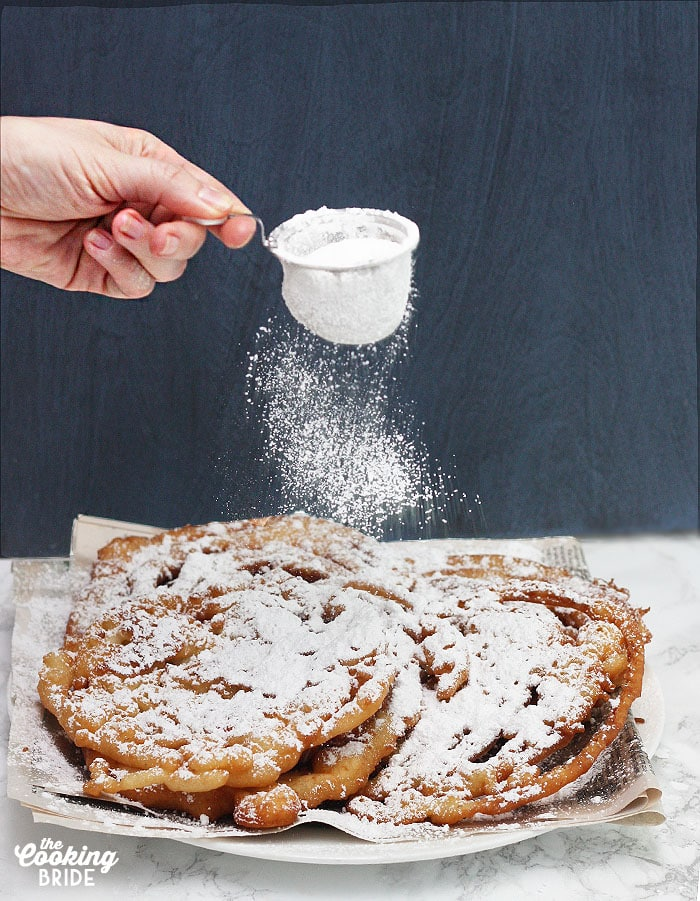 sprinkling powdered sugar over the funnel cakes