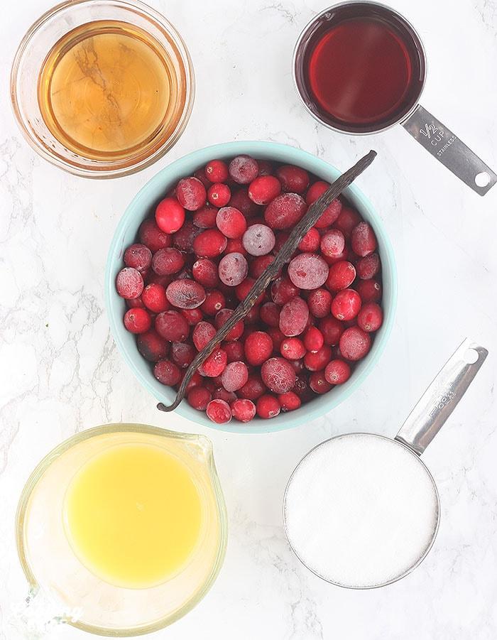 cranberry sauce ingredients including bourbon, cranberry juice, cranberries, vanilla bean, orange juice and sugar
