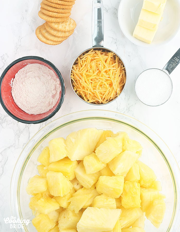 ingredients for pineapple casserole including pineapple chunks, flour, shredded cheese, Ritz crackers, butter and sugar