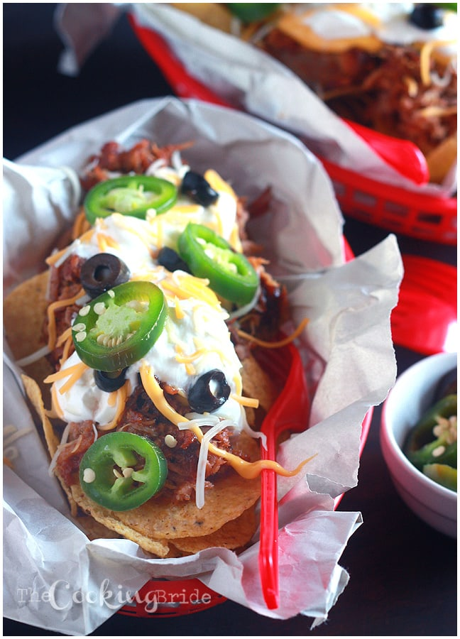 Loaded pulled pork nachos mixes sweet barbecue pulled pork drizzled with a spicy, creamy cheddar cheese sauce over toasted tortilla chips.