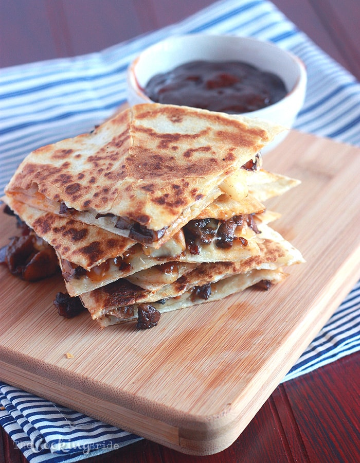 Mushroom Quesadillas  stacked on a wooden cutting board with a bowl of barbecue sauce in the background