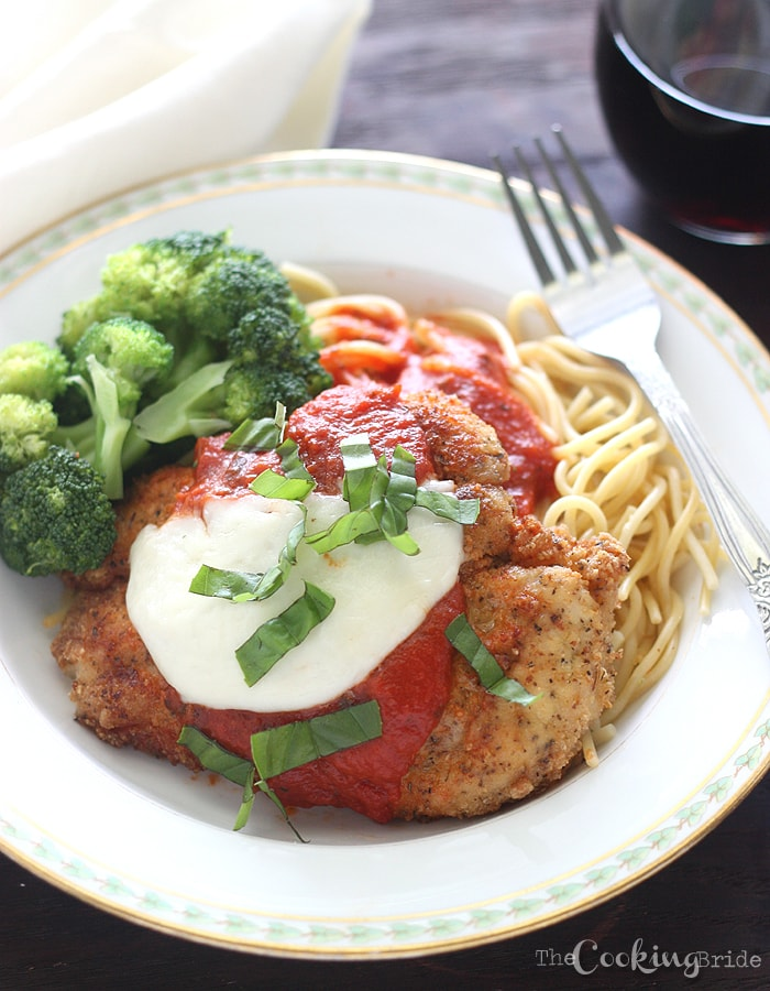 chicken parmesan on a white plate with a glass of rec wine in the background