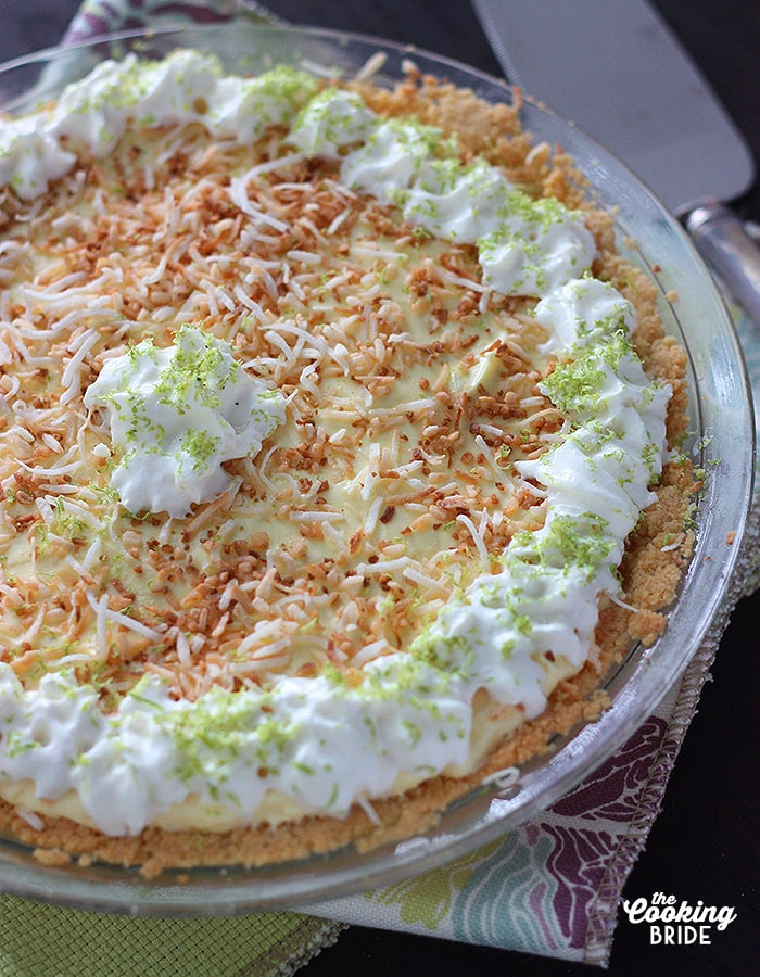 closeup shot of coconut lime icebox pie garnished with whipped cream and toasted coconut