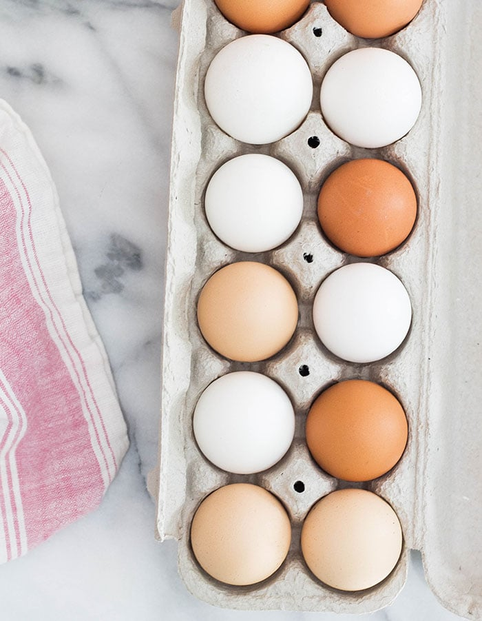 one dozen eggs in a carton on a marble background