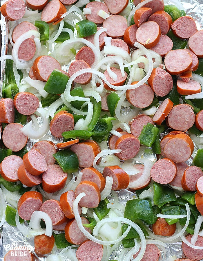 chopped sausage and veggies arranged on a foil lined baking sheet
